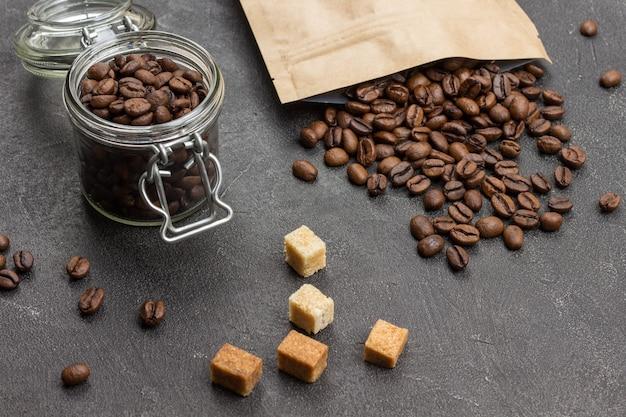 Grãos de café torrados em jarra de vidro e em saco de papel. pedaços de açúcar mascavo na mesa. vista do topo.