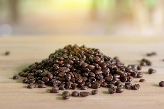 Grãos de café torrados em madeira com fundo de natureza.