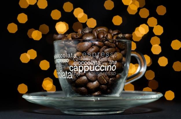Grãos de café torrados em um copo de vidro contra luzes amarelas de bokeh