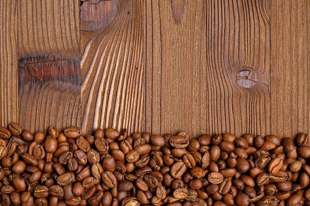 Grãos de café torrados em um fundo de madeira. vista do topo.