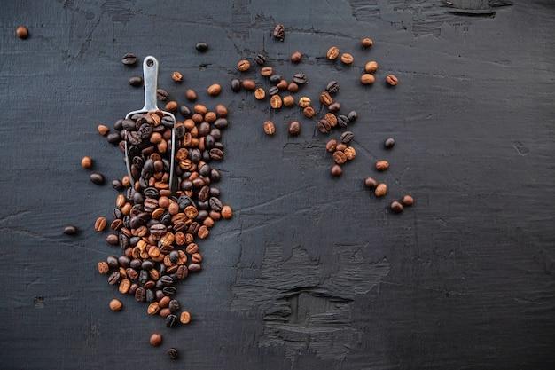 Grãos de café torrados em um fundo preto de madeira
