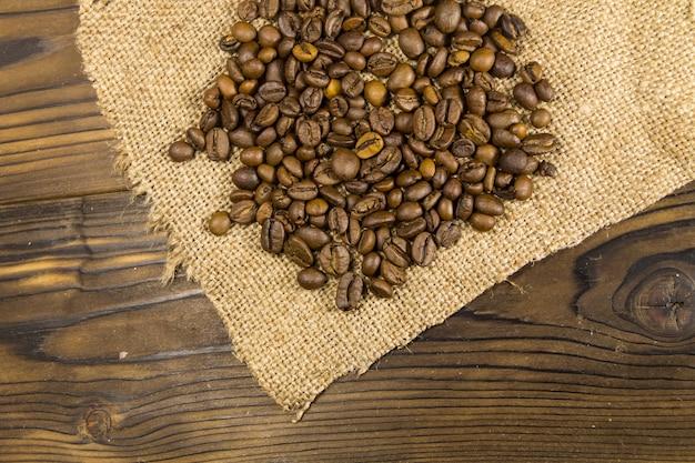Grãos de café torrados em um saco na mesa de madeira