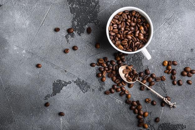 Grãos de café torrados em uma xícara cinza, plana com copyspace