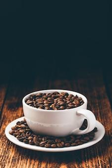 Grãos de café torrados em xícara branca sobre superfície de madeira rústica