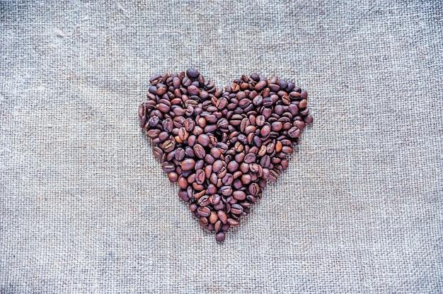 Grãos de café torrados empilhados no coração em um tecido plano