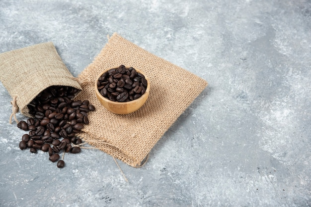 Grãos de café torrados fora do saco de estopa e em uma tigela sobre o mármore.
