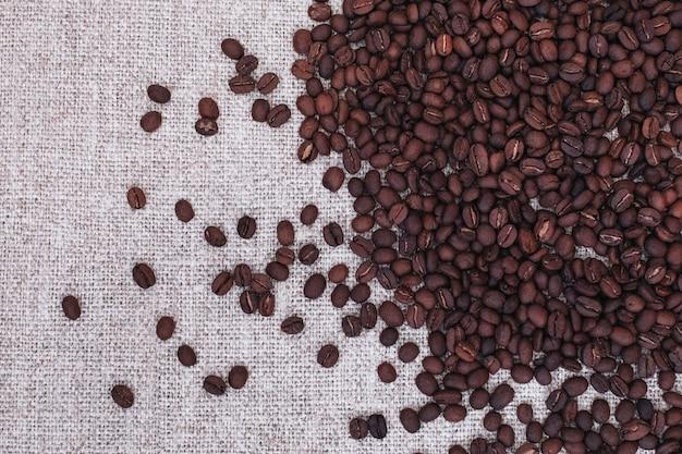 Grãos de café torrados frescos e aromáticos espalhados sobre um fundo bege de estopa. vista superior