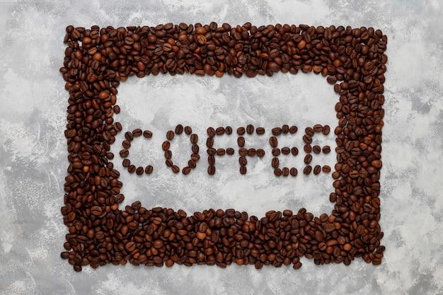 Grãos de café torrados frescos no concreto, vista superior, plana leigos