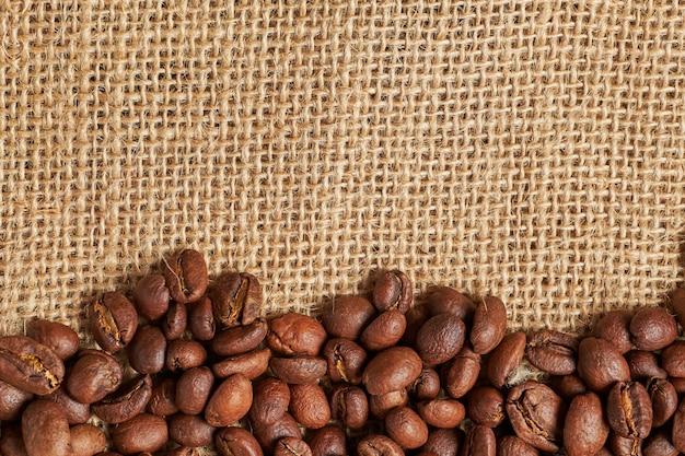 Grãos de café torrados mentem sobre um fundo de tecido de malha
