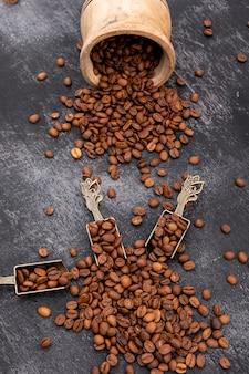 Grãos de café torrados na colher de metal na superfície preta