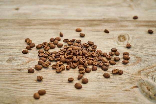 Grãos de café torrados na mesa de madeira