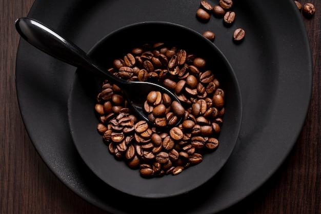 Grãos de café torrados na tigela com colher