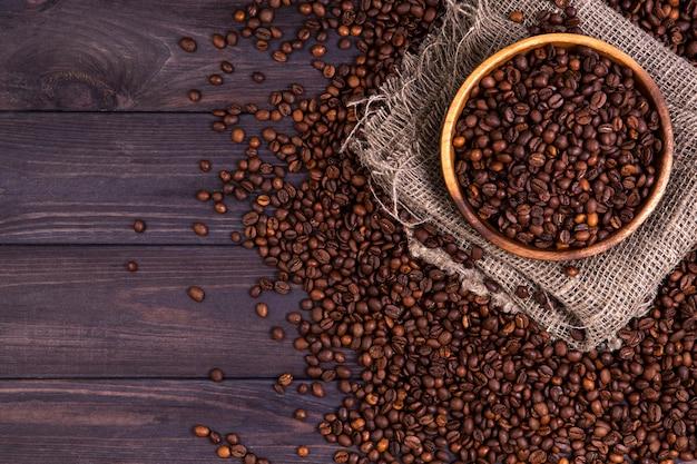 Grãos de café torrados na tigela no fundo escuro de madeira