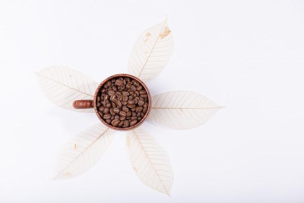Grãos de café torrados no copo de madeira sobre folhas secas