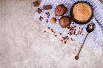 Grãos de café torrados; pedaços de chocolate; e bolinho no guardanapo sobre o velho cenário