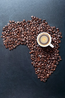 Grãos de café torrados que moldam o mapa da áfrica na lousa com uma xícara de café. conceito dos principais produtores de café do mundo.