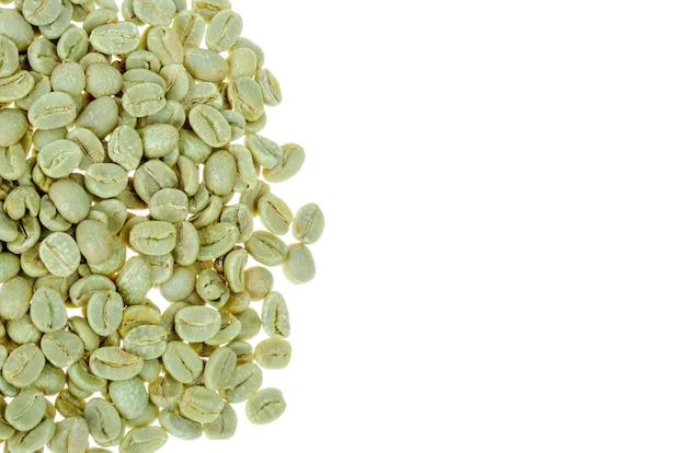 Grãos de café torrados verdes na parede branca