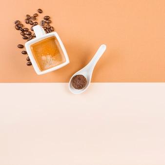 Grãos de café torrados; xícara de café e bola de chocolate na colher em pano de fundo duplo bege