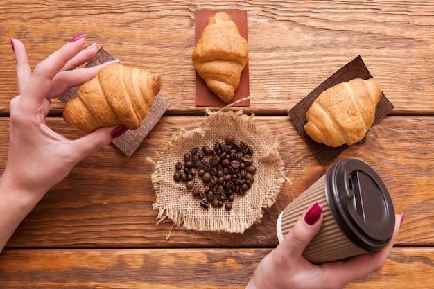 Grãos de café torrados, xícara na mão e sobremesas em fundo de madeira. closeup de sementes na mesa do café marrom escuro. vista do topo.