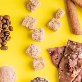 Grãos de café; trufas; cubos de açúcar mascavo e barra de chocolate de frutas secas em pano de fundo amarelo