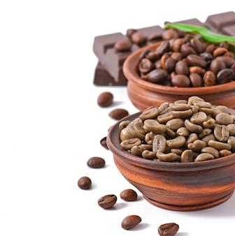 Grãos de café verdes e marrons em tigelas