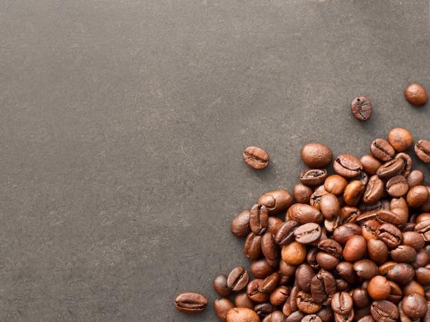 Grãos de café vermelhos e os grãos de café torrados isolados no fundo preto.