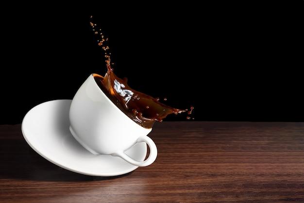 Grãos de café, xícara de café com efeito de respingo na mesa marrom