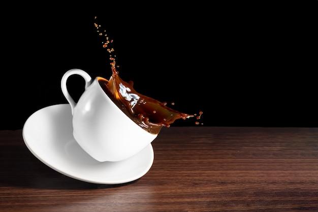 Grãos de café, xícara de café inclinado com efeito de respingo na mesa marrom