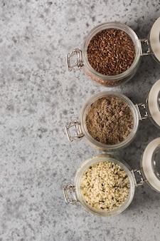 Grãos de cânhamo, linhaça marrom moída e linhaça em frasco de vidro na mesa de pedra cinza. vista do topo. espaço para texto.