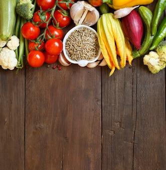 Grãos de centeio crus em uma tigela e vegetais na madeira