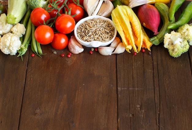 Grãos de centeio crus em uma tigela e vegetais na mesa de madeira