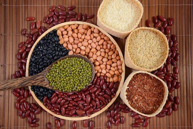 Grãos de cereais e sementes de feijão e arroz branco útil para a saúde em colheres de madeira.