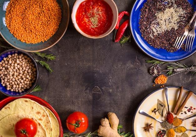 Grãos de cereais, feijões e especiarias tradicionais da culinária asiática ou oriental em pratos coloridos