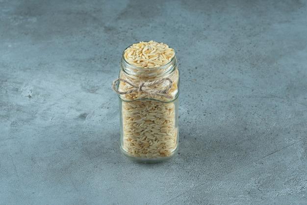 Grãos de macarrão em uma jarra de vidro com fundo azul. foto de alta qualidade