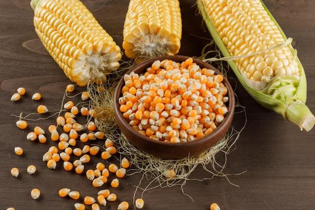 Grãos de milho com espigas em uma placa de argila na mesa de madeira, vista de alto ângulo.