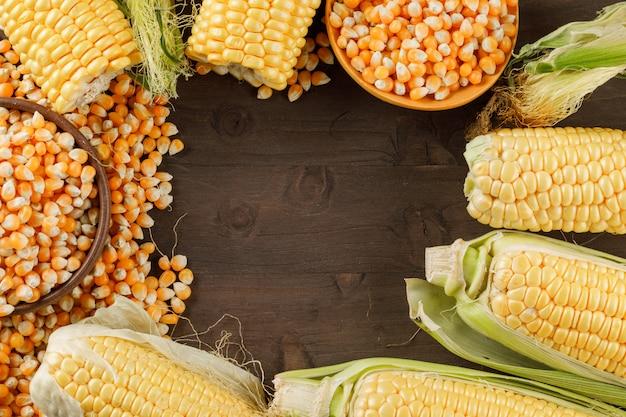 Grãos de milho com espigas na colher de pau e prato na mesa de madeira, configuração plana.