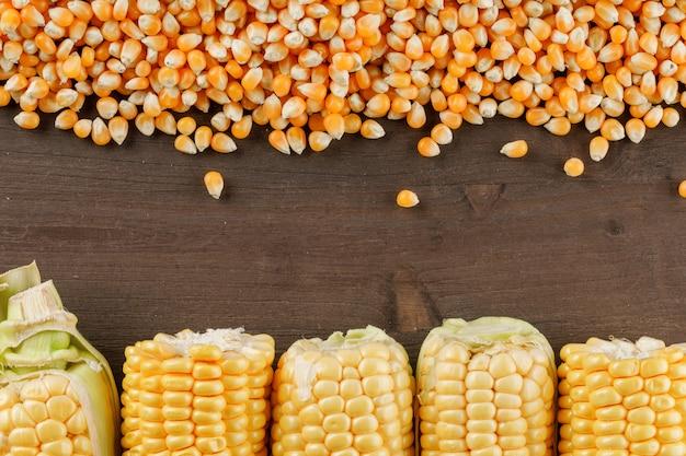 Grãos de milho com espigas na mesa de madeira, plana leigos.