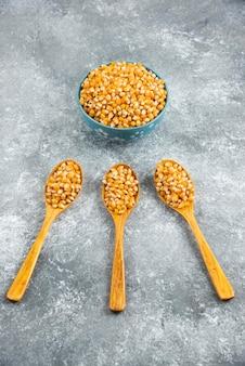 Grãos de milho crus em colheres e tigela.