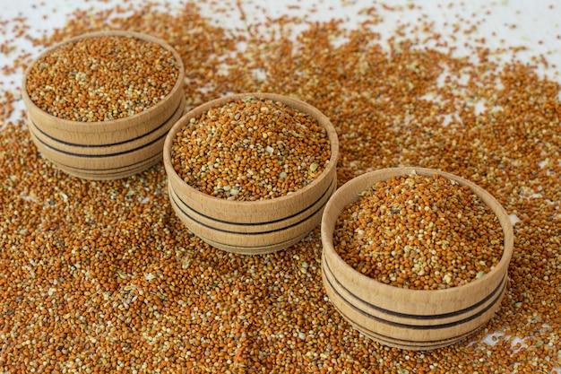 Grãos de painço em uma caixa de madeira. grãos de milho em um fundo branco