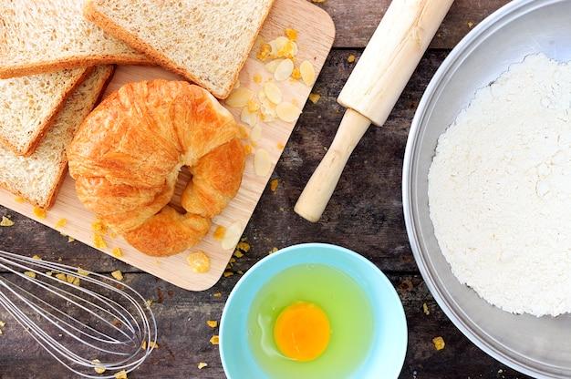 Grãos de pão e ingredientes em fundo de madeira