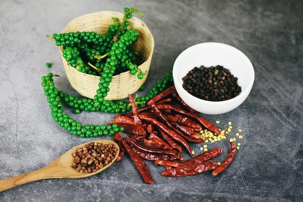 Grãos de pimenta na cesta e pimentas secas em fundo escuro