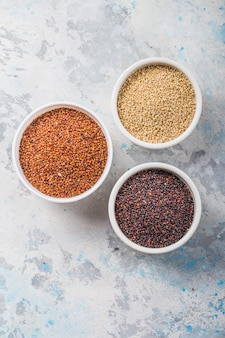 Grãos de quinoa preto, vermelho e branco em um prato fundo branco. comida saudável sem glúten. closeup de quinoa chenopodium