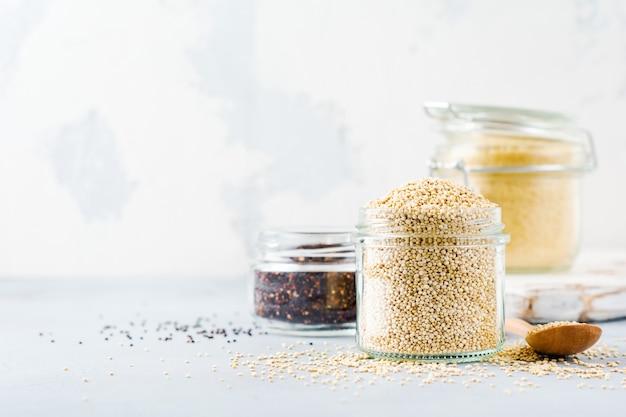 Grãos de quinua crus no frasco. comida vegetariana saudável na mesa da cozinha cinza. foco seletivo.