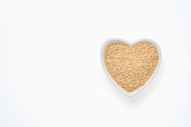 Grãos de quinua em uma tigela em forma de coração isolada na mesa branca, vista superior