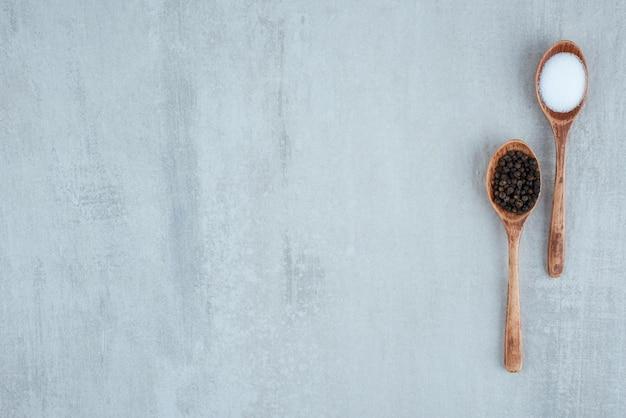 Grãos de sal e pimenta em colheres de madeira.