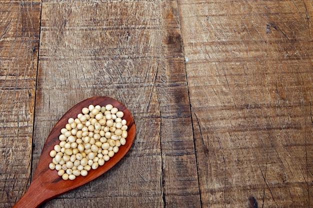 Grãos de soja na colher de pau com área para texto