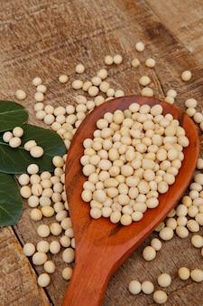 Grãos de soja na colher de pau com folhas de louro