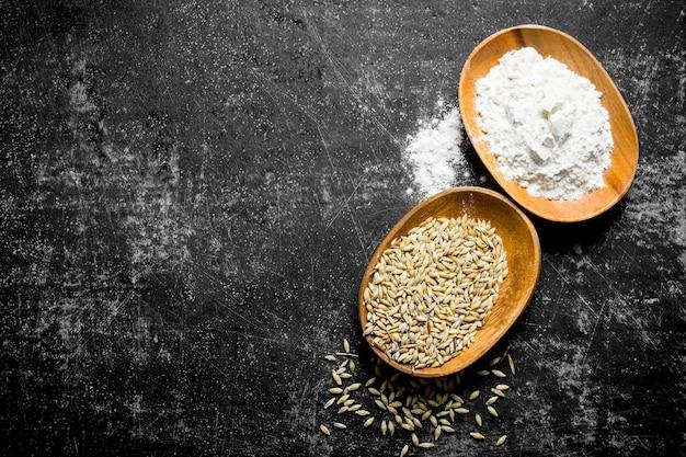 Grãos de trigo e farinha em tigelas na mesa rústica escura.