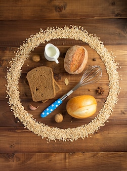 Grãos de trigo e ingredientes de panificação em fundo de madeira, vista superior
