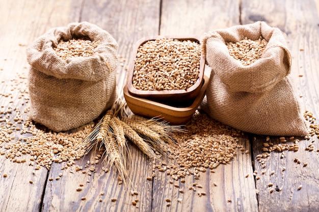 Grãos de trigo em sacos na mesa de madeira